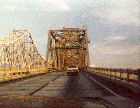 """Photo of sign on the northern approach that read, """"The W. E. 'Bill' Dean Bridge"""". Circa 1979. Submitted by Kai Warren. Photo taken by Barbara Andersen Lochridge."""