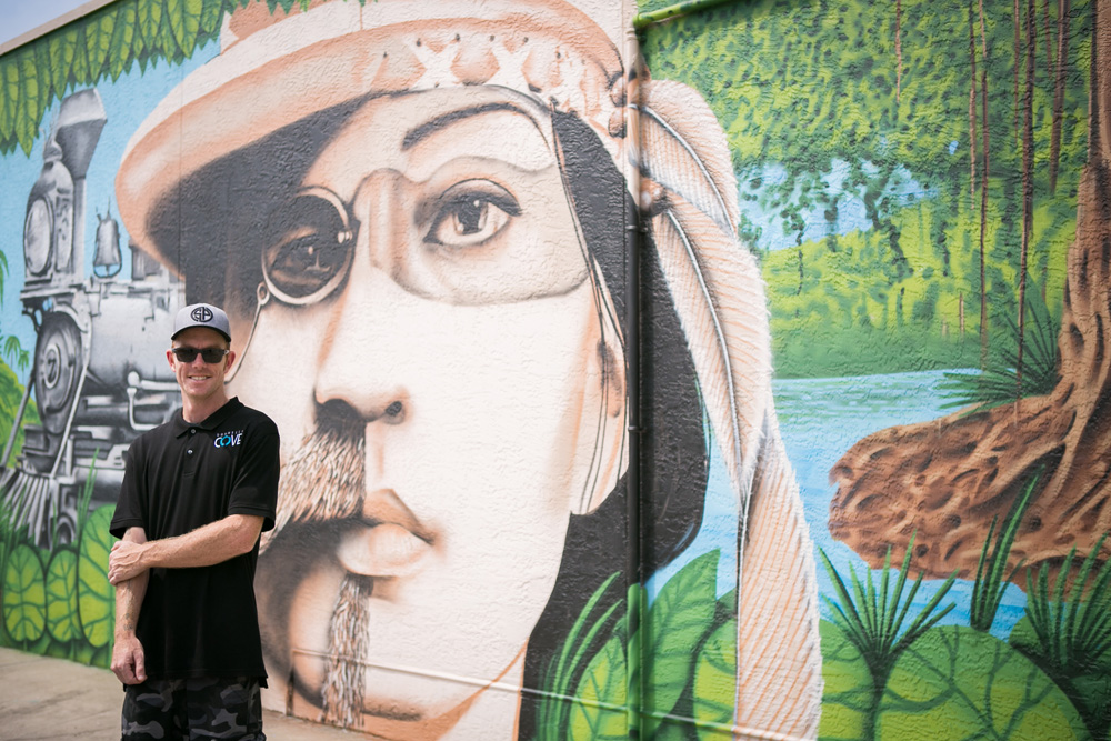 "Muralist Derek Donnelly standing in front of his masterpiece — ""Angels and Demens"" Photo by Andrejka Photography"